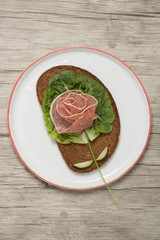 Sandwich with rose made of sausage on plate