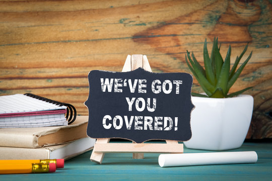 Weve got you covered. small wooden board with chalk on the table.