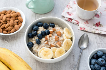 Healthy vegetarian breakfast Oatmeal Porridge Bowl with banana, blueberry and nuts and cup of green tea on gray background. Concept of healthy eating, healthy lifestyle, dieting, weight loss