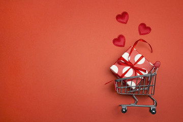 Shopping trolley with gift box, love hearts  and cope space on red background.