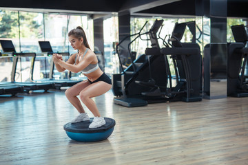 Woman training equilibrium in gym