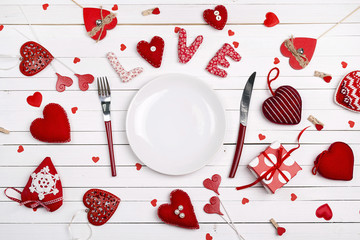 Festive table setting for Valentine's Day with fork, knife and hearts on a white wooden table.  Copy space.