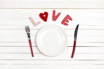 Love table setting with fork, knife and heart on a white wooden table. Copy space. T