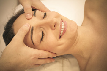 Esthetician massaging head and face of young woman. Close up.