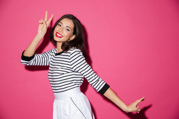 Portrait of a smiling woman showing peace gesture