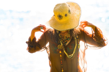 Pretty amazing free hippie girl outdoors, wearing a hat and accessories - Vintage effect photo