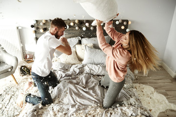 Affectionate couple and pillow fight at bedroom