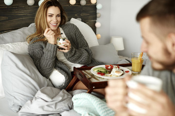 Cheerful woman eating in bed
