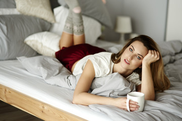 Dreamy woman with coffee reclining in bedroom