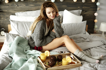 Woman sitting on bed next to breakfast