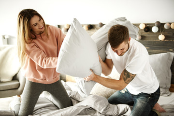 Cheerful couple enjoying at bedroom