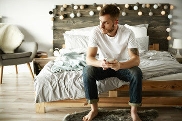 Man with mobile phone sitting on bed