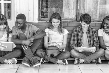 Multi ethnic group of teenagers using electronics and reading books seated in school hallway