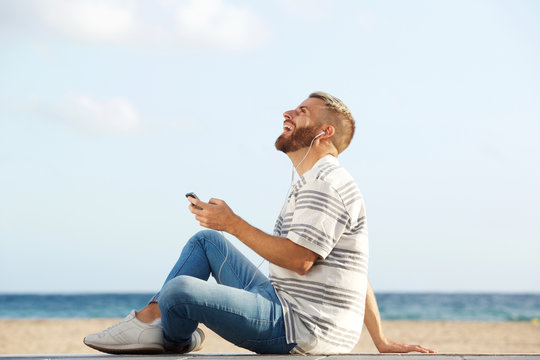 happy young man sitting by beach listening to music with mobile phone and earphones