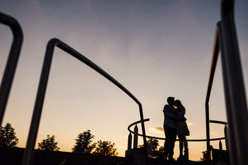 Silhouette of a couple hugging close to a circular staircase at dusk