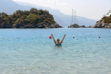 Woman is in shallow water of sea beach , Oludeniz, Turkey.