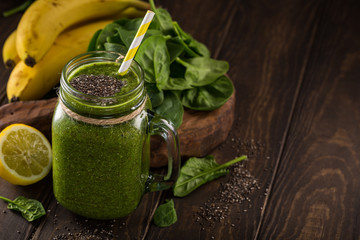 Healthy breakfast with green smoothie in glass jar and ingredients. Detox, diet, healthy, vegetarian food concept with copy space. Dark photo, high angle view.