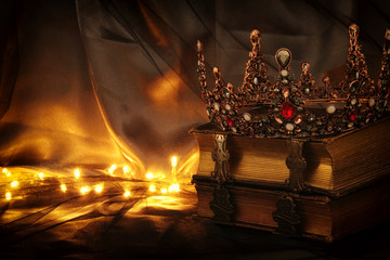 low key image of beautiful queen/king crown on old book. fantasy medieval period.