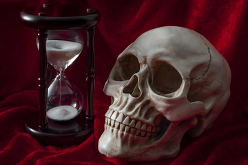 Ephemerality of life, fear of death and Memento Mori concept with a skull and vintage hourglass on red velvet background
