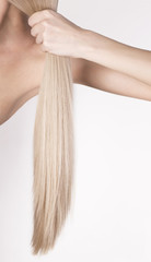 Healthy platinum blonde hair in a tale. Girl holding her hair in a hand.