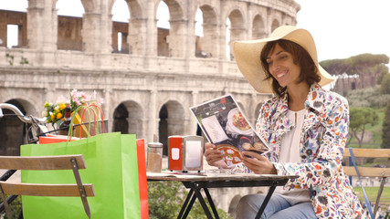 Beautiful young woman tourist reading menu sitting at the table of a bar restaurant in front of the Colosseum in Rome. Elegant dress with large hat and colorful shopping bags on a summer day.