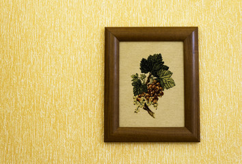 A embroidered picture hanging on the wall. A embroidery in retro style.
