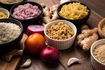 Ginger, Garlic, onion and tomato paste and powder in and raw form. Group of Basic Indian food ingredients over wooden background. Selective focus