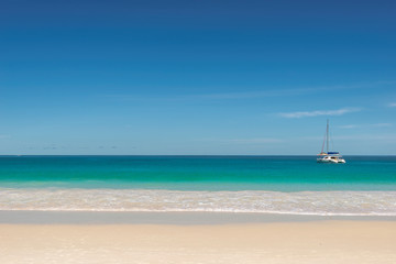 Tropical beach background with sailboat on horizon.