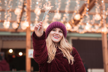 Pleased blonde girl dressed in stylish clothes, holding glowing sparklers at the Christmas fair in Kiev