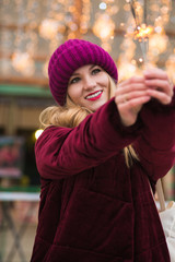 Cheerful blonde girl dressed in stylish clothes, holding glowing sparklers at the Christmas fair in Kiev