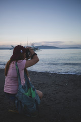 Girl holding a camera, taking a shot at the sky