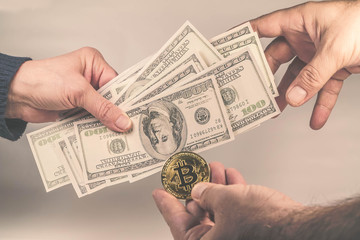 Golden Bitcoins on US dollars in the hands . Electronic money exchange concept