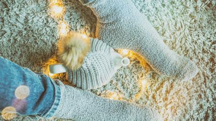 Frauenbeine in Jeans mit Teekanne auf grauem Teppich