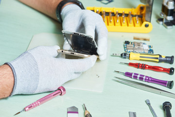 smart phone repair. repairman disassembling smartphone