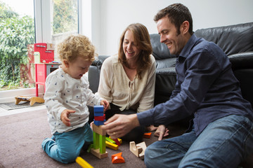 Parents and baby boy playing with building blocks