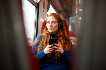 Woman on train listening to music on mobile phone with headphones, London
