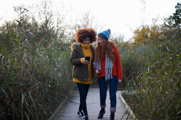 Friends on walkway in tall grass looking at smartphone