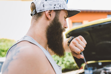 Young male hipster making smartwatch phone call on road trip, Como, Lombardy, Italy