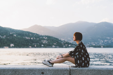 Young woman sitting on waterfront wall at Lake Como, Lombardy, Italy