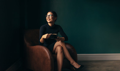 Businesswoman sitting on armchair with cup of tea
