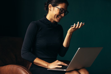 Smiling woman speaking on smartphone and working on laptop