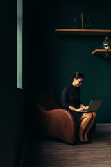 Businesswoman in armchair working on laptop