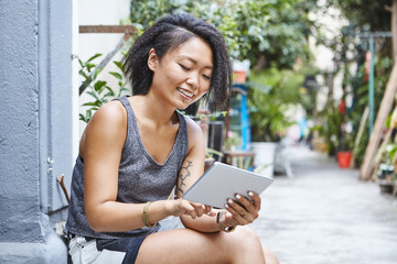 Woman sitting on doorstep in residential alleyway looking at digital tablet, Shanghai French Concession, Shanghai, China