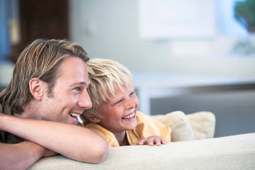 Father and son relaxing on sofa, looking away smiling