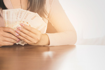 Asian business woman hand  holding money planing to invest or paying , can be used for saving ,debt,payment concept background