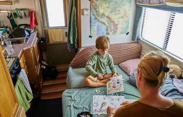 Mother and son cutting out pictures in campervan, Chuquisaca, Bolivia, South America