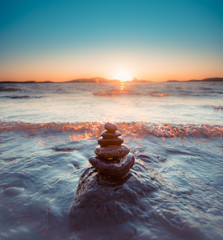 Photo sur Plexiglas Zen pierres a sable Round smooth stones in pyramid form by sea with wave coming in during golden sunset