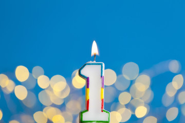 Number 1 birthday celebration candle against a bright lights and blue background