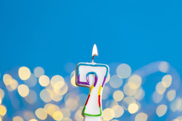 Number 7 birthday celebration candle against a bright lights and blue background