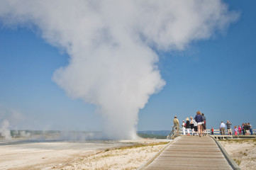 People visiting Yellowstone national park, wooden path an steam from a hot spring